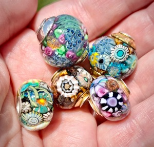 Handful of encased murrini beads with sterling silver cores and bead caps